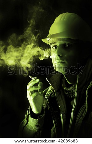 Construction worker smoking isolated in black - stock photo