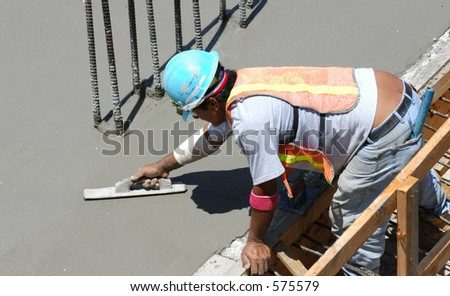 Construction worker smooths concrete - stock photo