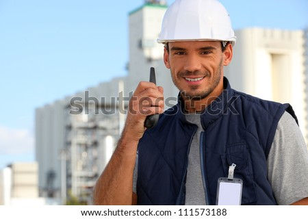 Construction worker speaking into his walkie-talkie - stock photo