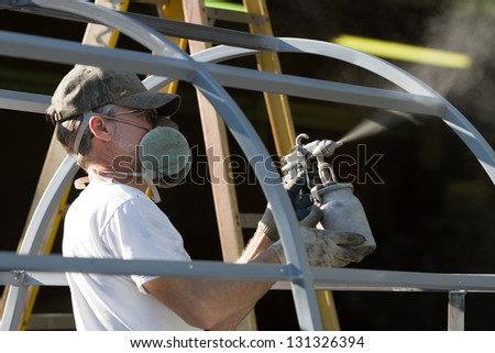 Construction worker spray paints while wearing respiratory safety equipment to protect himself from the fumes at a factory. - stock photo