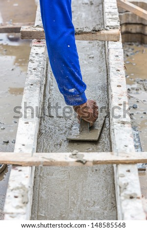 Construction worker spreading wet concrete on the beam casting - stock photo