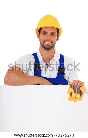 Construction worker standing behind white wall. All on white background. - stock photo