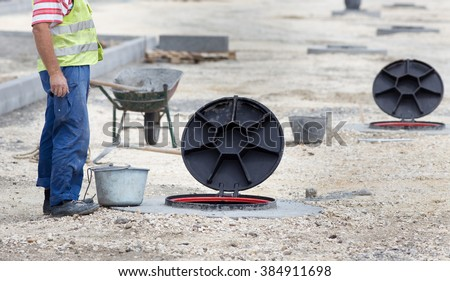 Construction worker standing beside manhole with open cover at building site - stock photo