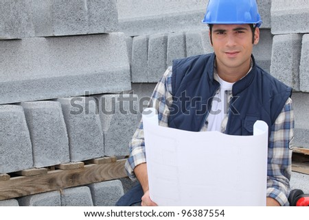 Construction worker standing next to pallets of concrete curb while looking at some plans - stock photo