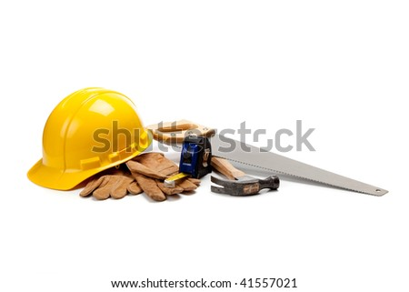 Construction worker supplies including a yellow hard hat, tape measure, box cutter, screw drivers, hammer and work gloves on a white background - stock photo