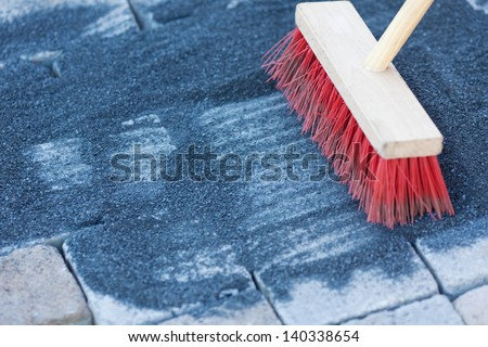 Construction worker sweeping up on rough concrete at a new pavestones using a large broom - stock photo