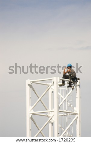 Construction worker takes a break while building crane - stock photo