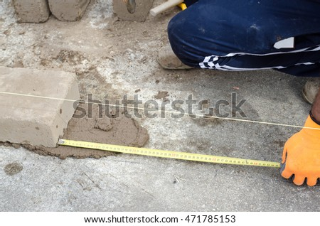 Construction worker takes measures for laying bricks of the wall. Construction site