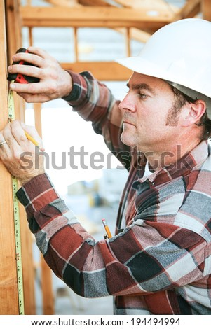 Construction worker taking measurements on the job site.   - stock photo