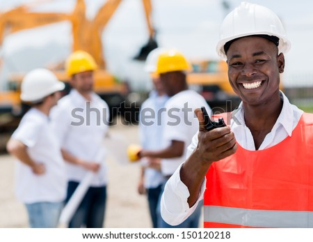 Construction worker talking on a radio and looking happy  - stock photo