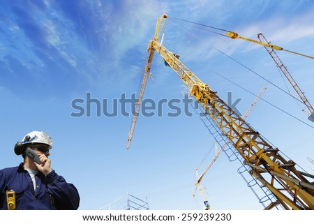 construction worker talking to crane driver inside building site - stock photo