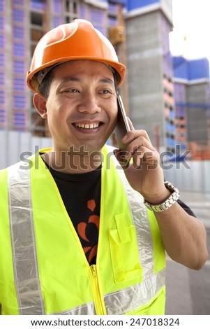 Construction worker talking with mobile phone - stock photo