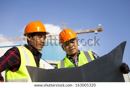 Construction worker team checking a plan work flow  - stock photo