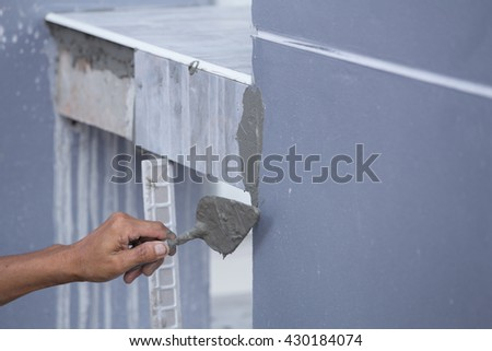 construction worker tiler is tiling, ceramic tile floor adhesive, trowel with mortar - stock photo