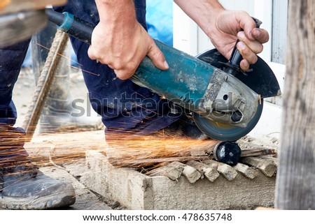 Construction worker using a grinder cuts steel rods