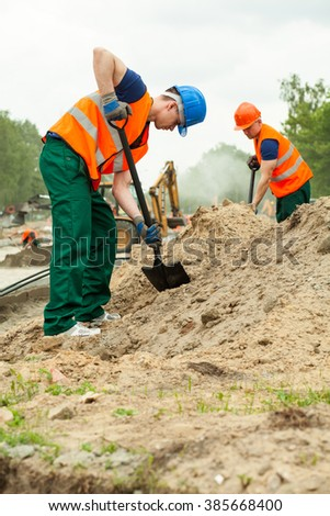 Construction worker using a spade to dig  - stock photo