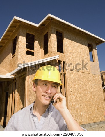 Construction worker using cell phone near unfinished building - stock photo