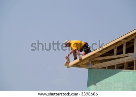Construction worker using circular saw on roof of new home to trim excess from edge of roof
