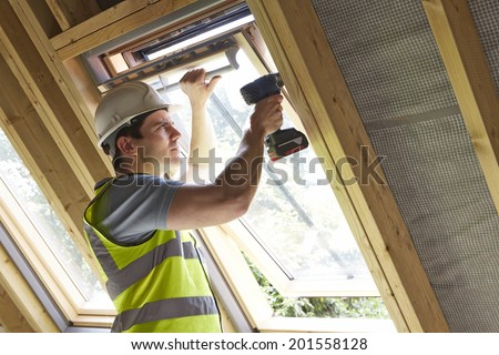 Construction Worker Using Drill To Install Window - stock photo