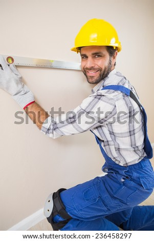 Construction worker using spirit level in a new house