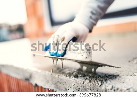 construction worker using steel trowel for plastering - stock photo