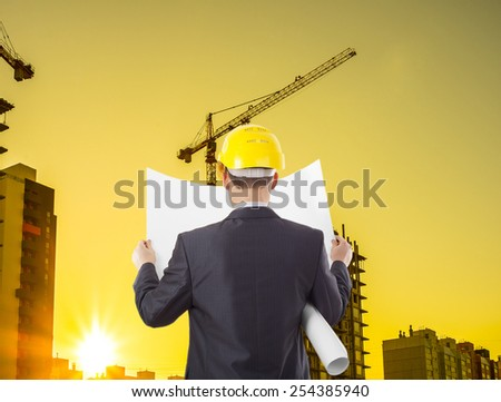 construction worker wearing hard hat.back view worker or engineer with yellow helmet for workers security holding in hands paper plan on the background of a new home dwelling house building - stock photo