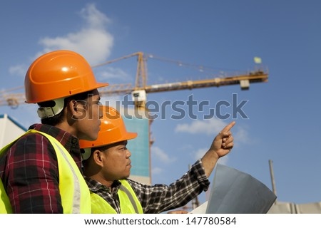 Construction worker wearing protective clothing discussion on location site and yellow crane on the background