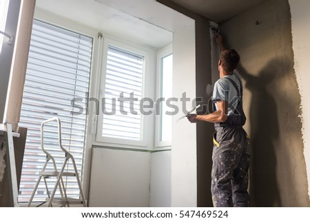 Construction Worker Wearing Worker Overall With Wall Plastering Tools  Renovating Apartment House. Plasterer Renovating Indoor