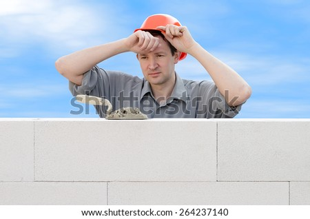 Construction worker wiping the sweat from his forehead - stock photo
