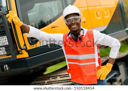 Construction worker with a crane at the background  - stock photo