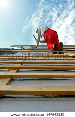 construction worker with a hammer on the roof - stock photo