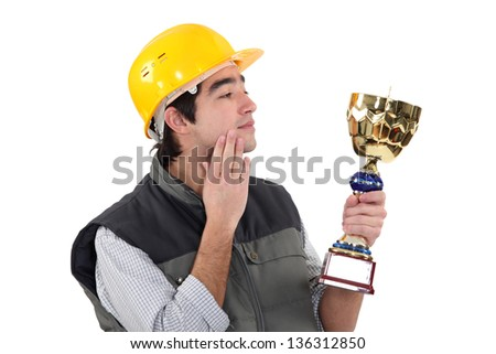 Construction worker with a trophy - stock photo