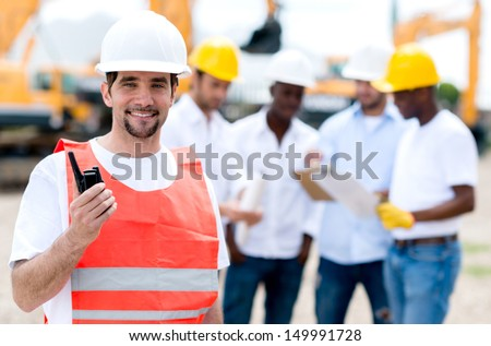 Construction worker with a walkie talkie at a building site  - stock photo