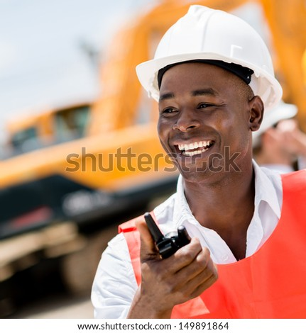 Construction worker with a walkie-talkie looking very happy  - stock photo