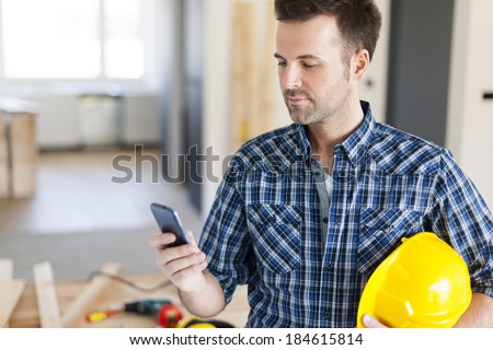 Construction worker with contemporary mobile phone  - stock photo