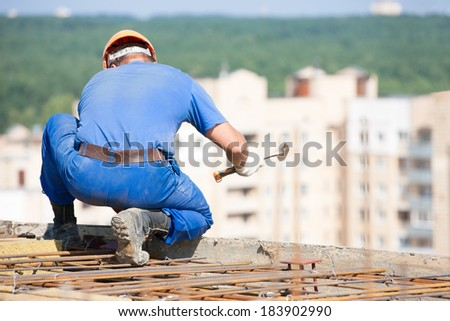Construction worker with hammer mounting formwork during concrete works - stock photo