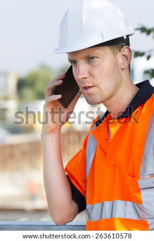 Construction worker with helmet working outdoor at a building site for a new road  - stock photo