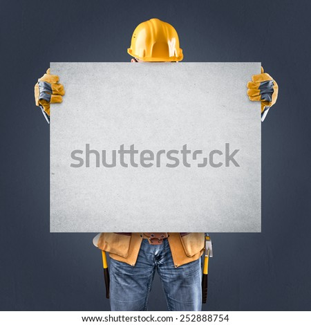 construction worker with information posters on a blue background - stock photo
