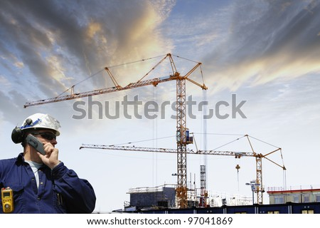 construction worker with large building site in background, sunset - stock photo
