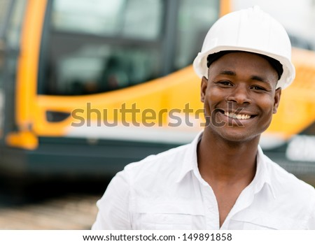 Construction worker with machines at the background looking happy  - stock photo
