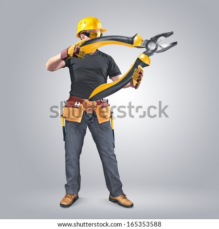 construction worker with tool belt and pliers - stock photo