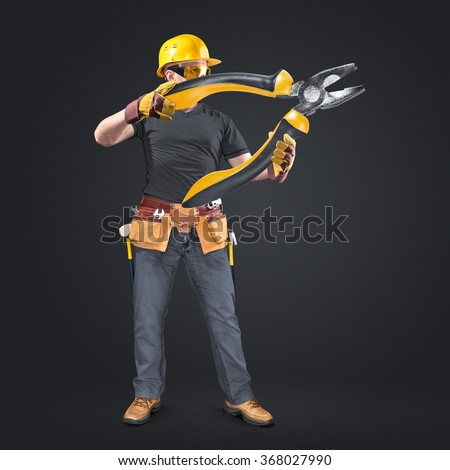 construction worker with tool belt and pliers on dark background - stock photo
