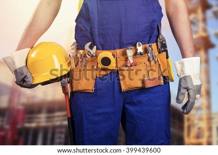construction worker with tool belt at building site - stock photo
