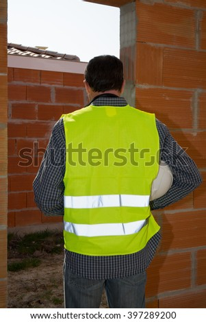 Construction worker with white helmet looking at the new building - stock photo