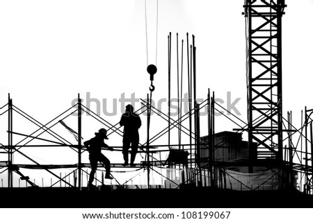 Construction workers and crane seen in outline