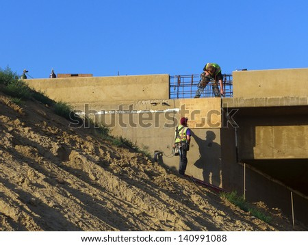Construction workers are putting the finishing touches on a freeway bridge before allowing access to public traffic - stock photo