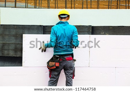 construction workers at a construction site when the building insulation - stock photo