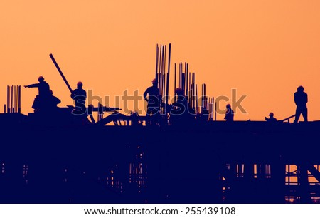 Construction workers at sunset. - stock photo