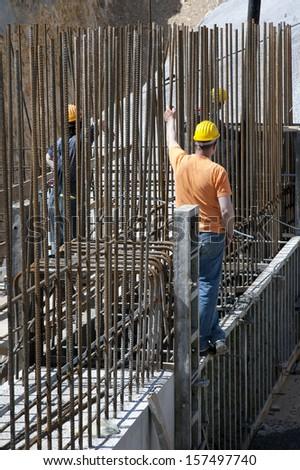 Construction workers between steel bars - stock photo