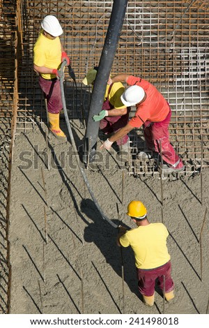 Construction workers casting foundations of hydro power plant - stock photo